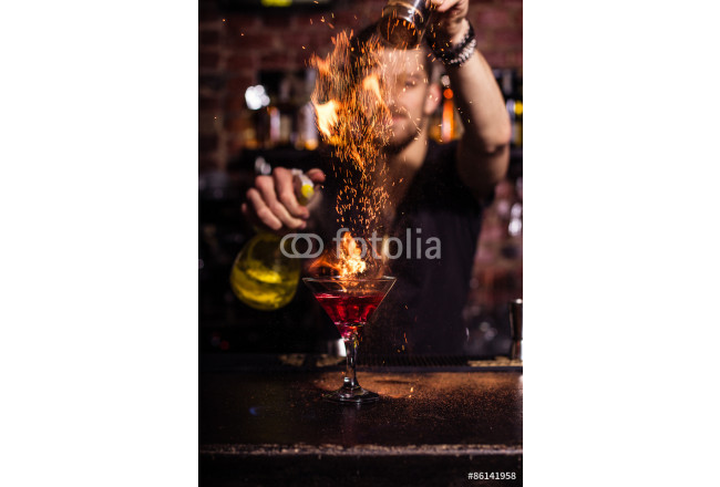 The bartender makes a cocktail of fire. 64239