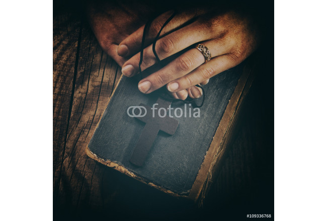 closeup of hands holding vintage cross on Bible 64239