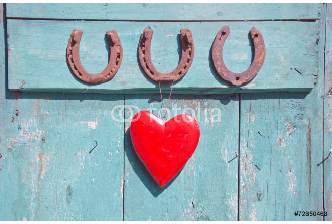 three old rusty horseshoe luck symbol and red heart on door 64239