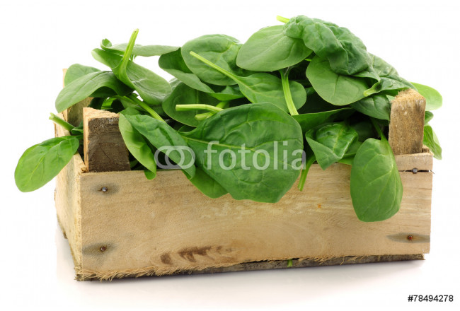 wooden box with fresh spinach leaves on a white background 64239