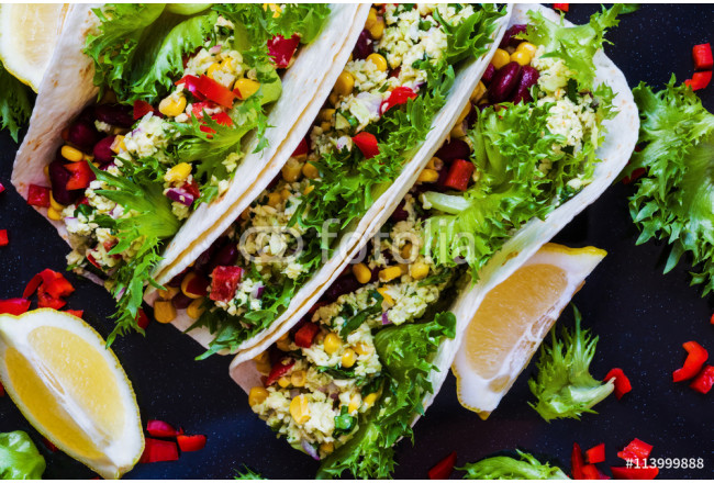 Vegetarian tacos with guacamole, corn, black beans and red peppers. On black background, top view. 64239