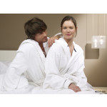 Couple in bathrobes sitting on bed. 64239