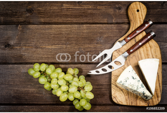 Two kinds of cheese and stainless steel cheese knife and fork with wood handle are is lying on the board of olive wood. Grapes are lying on a wooden board. 64239