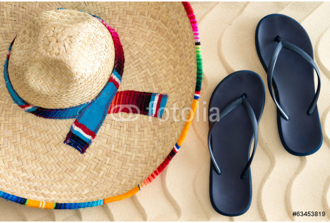Straw sombrero and sandals on beach sand 64239