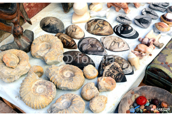 Selection of head masks and ammonite on a traditional Moroccan market (souk) in Marrakech, Morocco 64239