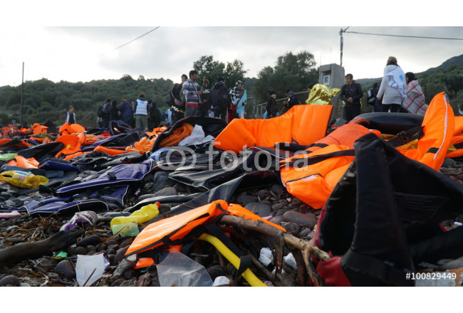Abandoned belongings and life jackets on the shore 64239