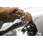 A man using repairing equipment to fix damaged windshield 64239