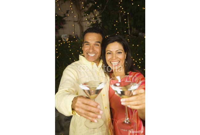 Hispanic couple toasting with cocktails at night 64239