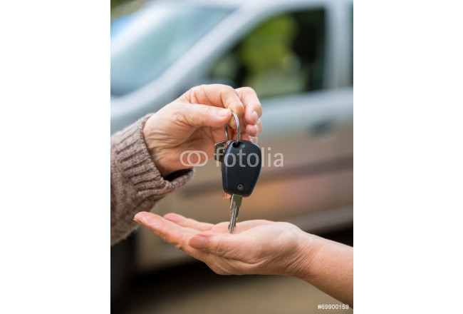 Woman giving keys from a car to another woman 64239