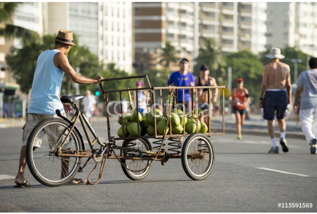 Street vendor delivering green coconuts from a cart on the beachfront street in Copacabana Beach 64239