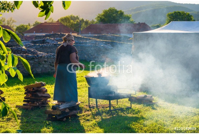 Woman cooking romanian traditional food on fire outdoor in a camping holiday of ulpia traiana, sarmisegetusa in summer season 64239