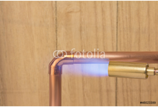 Plumbers hot gas soldering burner heating a copper pipe 64239